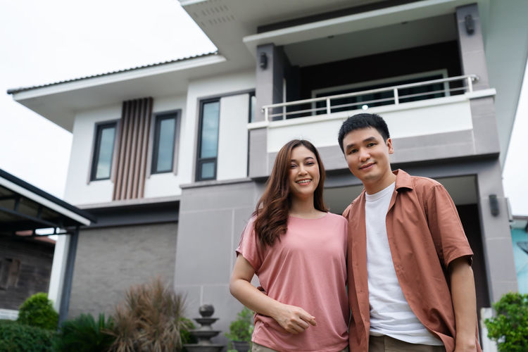 Young couple standing against building