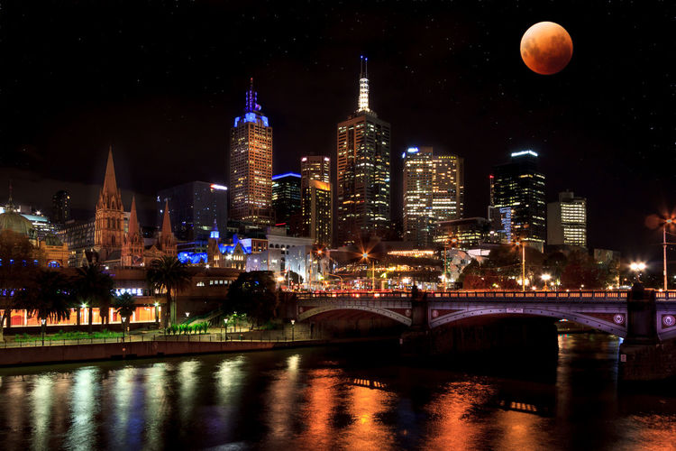 Illuminated buildings in melbourne city with super moon reflected over the yarra river at night