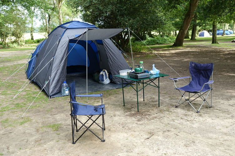 Empty chairs with table and tent at campsite in forest