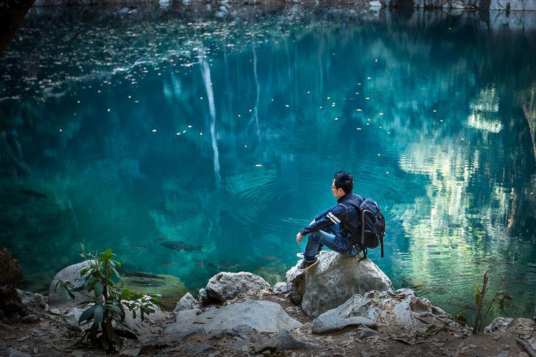 Full Length Of Backpacker Sitting On Rocks By Lake
