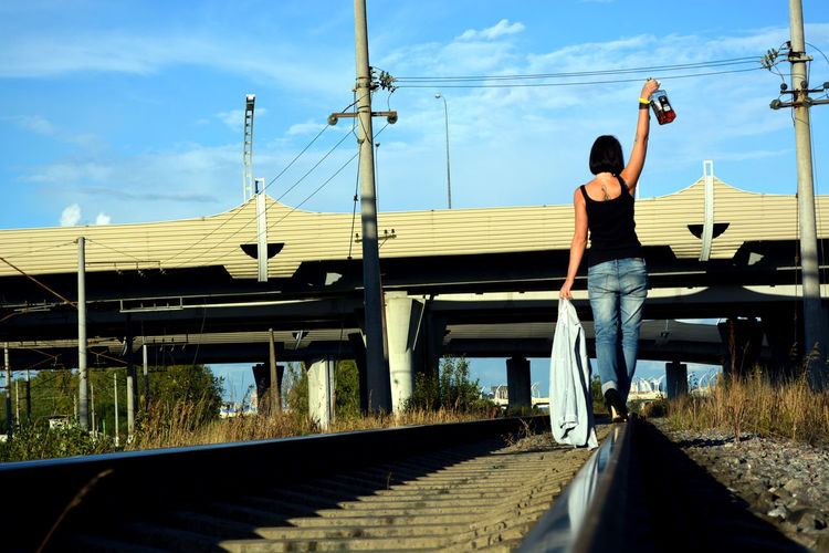 Rear view of drunk woman walking on railroad track while holding liquor bottle