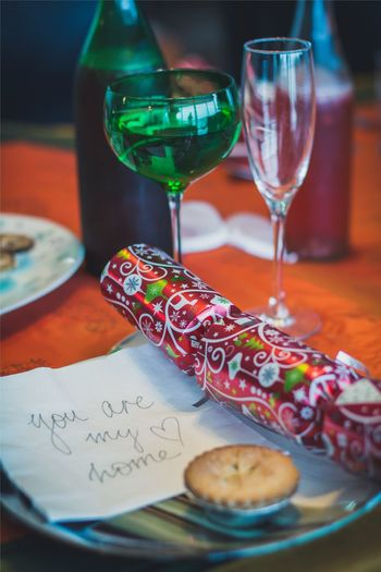 Close-Up Of Christmas Cracker In Plate With Text On Paper