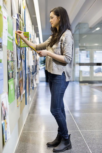 Full length of woman standing on book at store