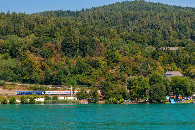 WORTHERSEE, AUSTRIA - AUGUST 08, 2018: Great scenery from the boat to the shore line of the lake, beautiful buildings, mountains, forests, highways. Tourists who enjoy a variety of water recreation types. Nature Day Outdoors Austria Carinthia Carinthian Lakes Tourist Tourists Lake Wörthersee Recreation  Leisure Landscape Water Sea Boats Motorboat Speedboats Summer People Holidays Fun Travel Beach Resort Lifestyle Sunny Rest Joy Waves Europe Alps Alpine Alpine Lake Tree Plant Architecture Transportation Waterfront Beauty In Nature Nautical Vessel Green Color Built Structure Scenics - Nature Growth Land Building Exterior Mode Of Transportation Foliage No People