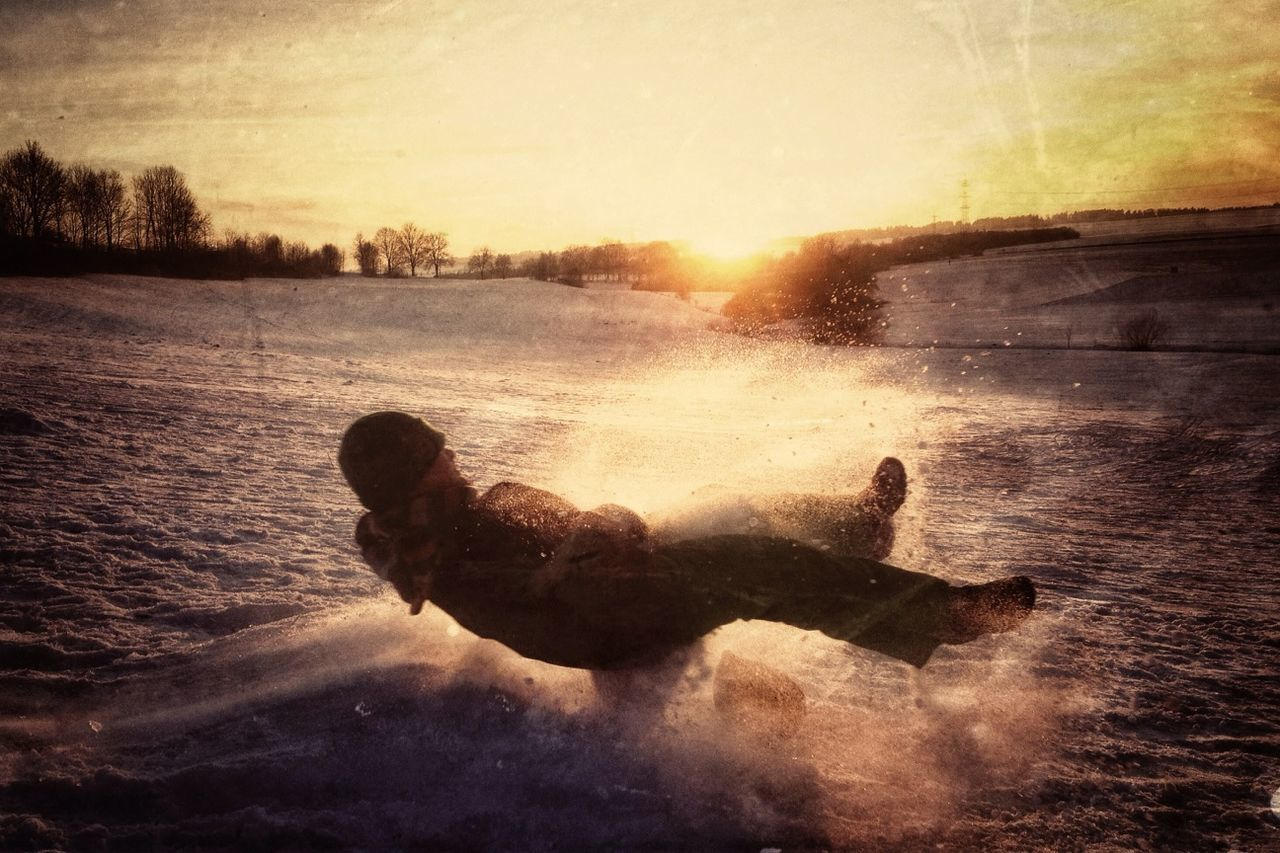Full length of man riding sled on field against sky at sunset during winter