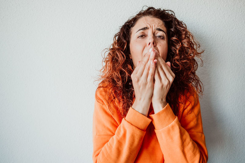 Woman sneezing while standing against wall