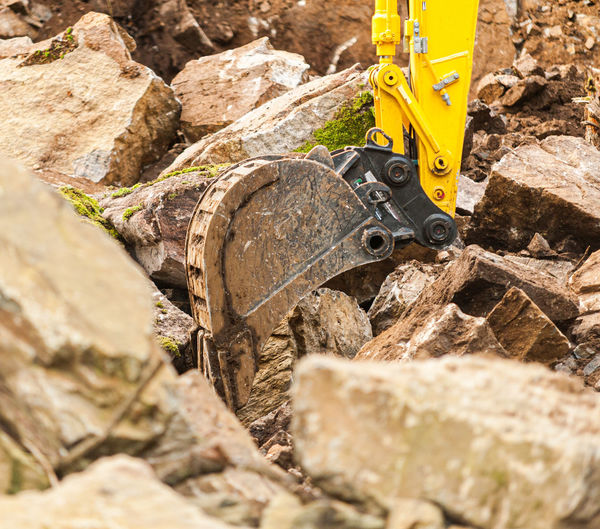 Close-up of yellow machinery on rock at construction site