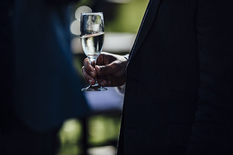 Midsection of man holding wine glass