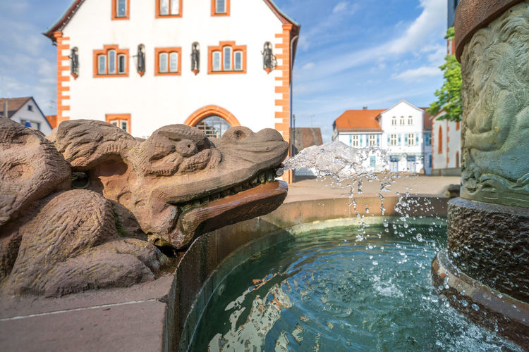 Statue of fountain by buildings in city