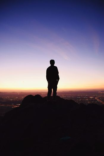 Rear view of silhouette man standing on rock against sky during sunset