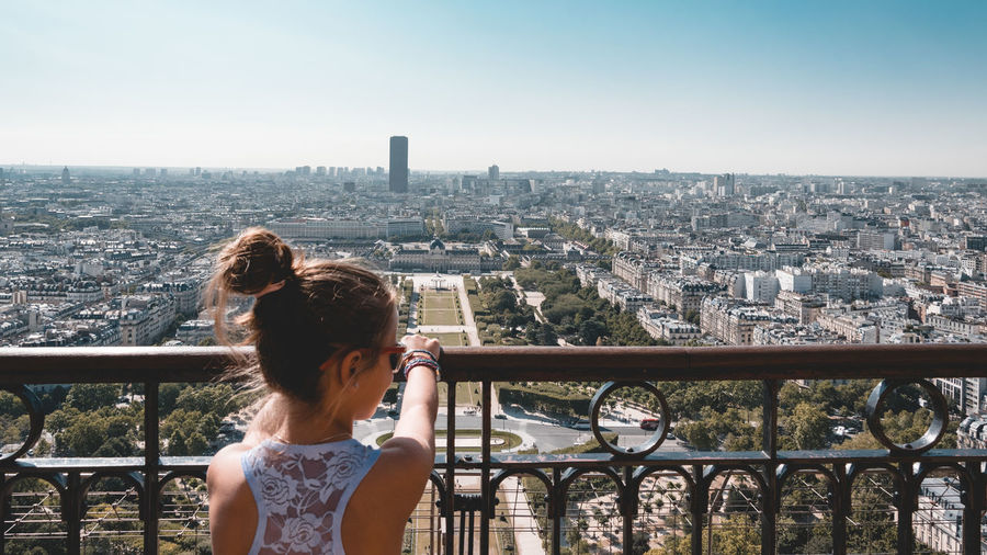 Rear view of girl looking at cityscape against clear sky