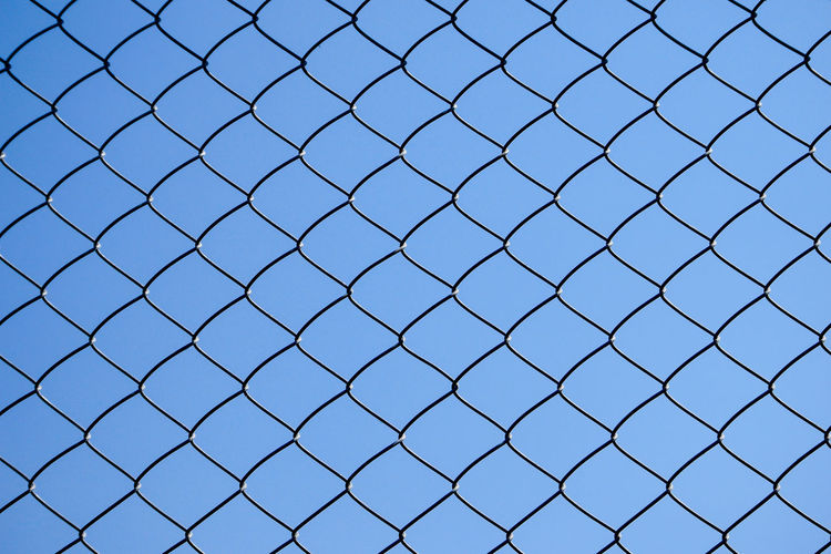 Security Backgrounds Full Frame Fence Pattern No People Protection Safety Boundary Barrier Metal Chainlink Fence Day Blue Nature Sky Close-up Outdoors Grid Built Structure Crisscross