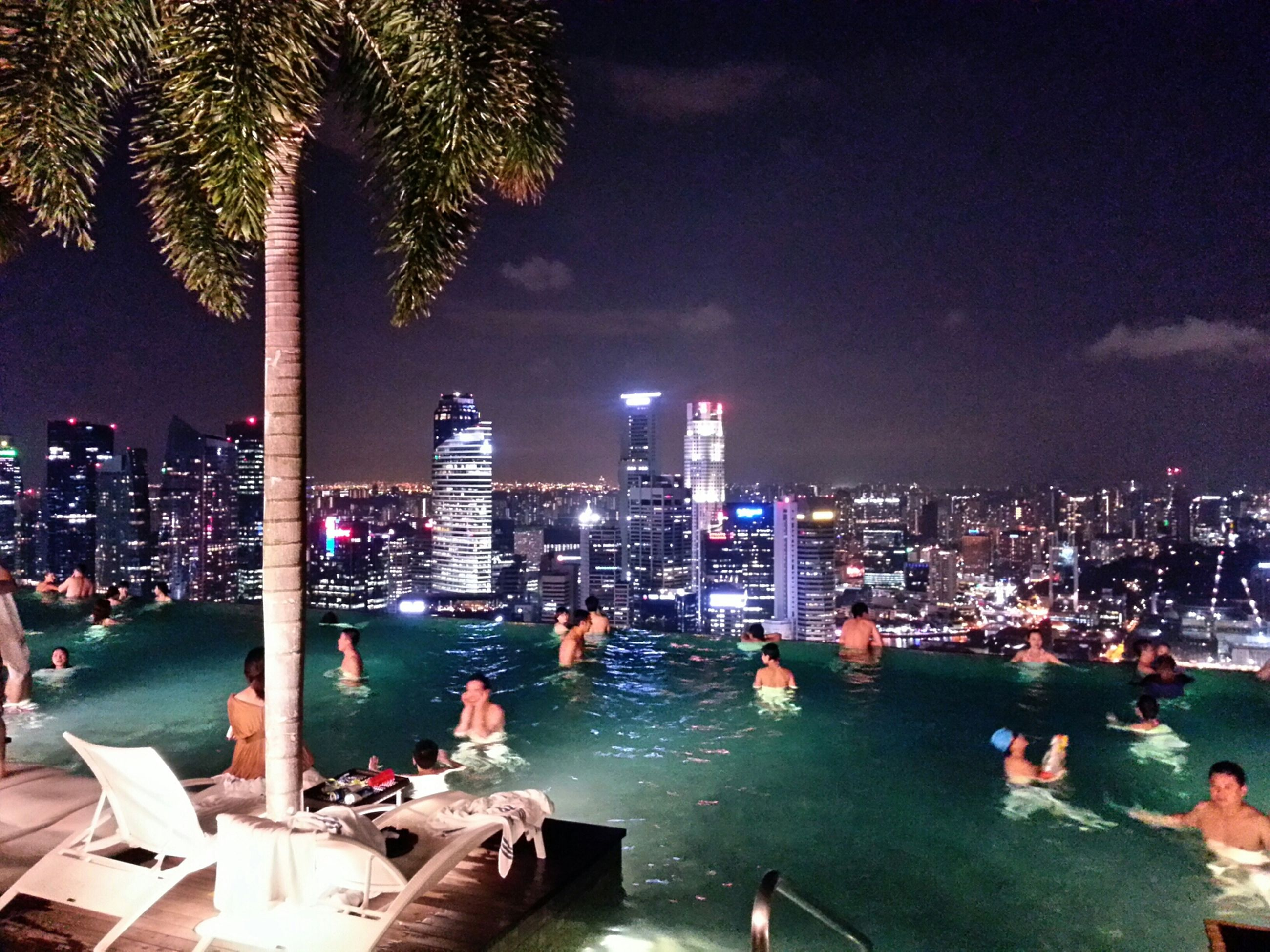 city, building exterior, illuminated, cityscape, architecture, skyscraper, built structure, night, water, sky, tall - high, modern, tower, city life, urban skyline, leisure activity, office building, financial district, lifestyles