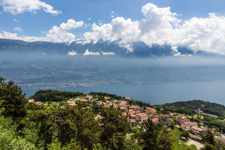 Lago di Garda with Monte Baldo Lago Di Garda Gardasee Gardalake Alps Italy Lake Lake View Water Village Panorama Sky Cloud - Sky Beauty In Nature Scenics - Nature Tree Architecture Nature Building Exterior Day Plant Built Structure Tranquil Scene No People Environment Tranquility Mountain Building Outdoors