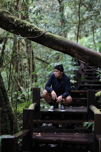 Young man sitting on wood in forest