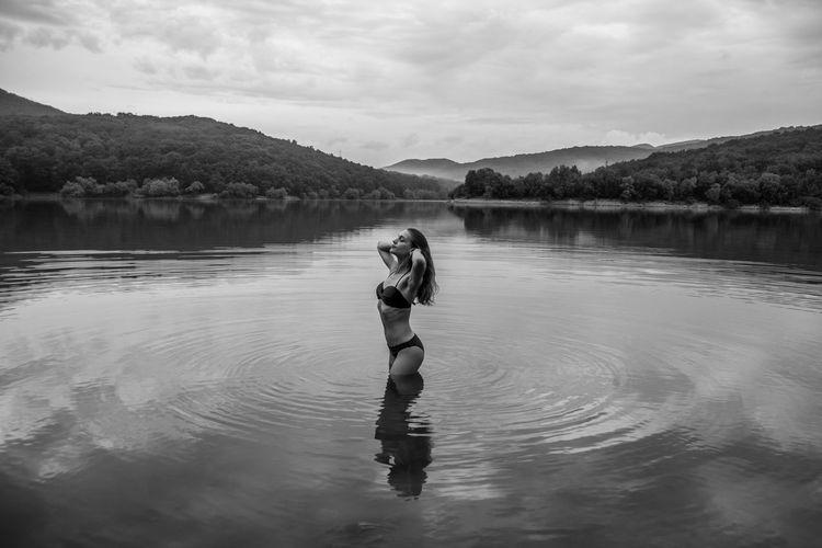 Woman Standing In Lake Against Sky
