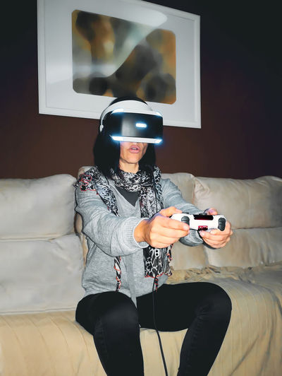 Woman with virtual reality headset sitting on the couch at home. Fun Simulator Equipment Adult Play Girl Visual Simulation Display Vision Backgrounds Gaming Concept Futuristic Future Game Young Women Woman Entertainment Device Screen Modern Digital Innovation Headset Glasses Technology Vr Virtual Reality Headset Virtual Reality Virtual Reality Simulator Virtual
