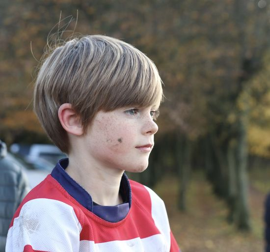 Close-up portrait of boy looking away outdoors
