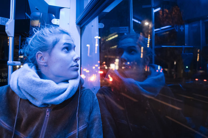 Young woman looking through window in vehicle at night