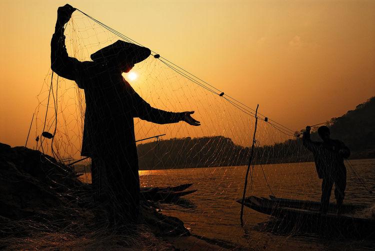 Silhouette Men Holding Fishing Net Against Sky During Sunset