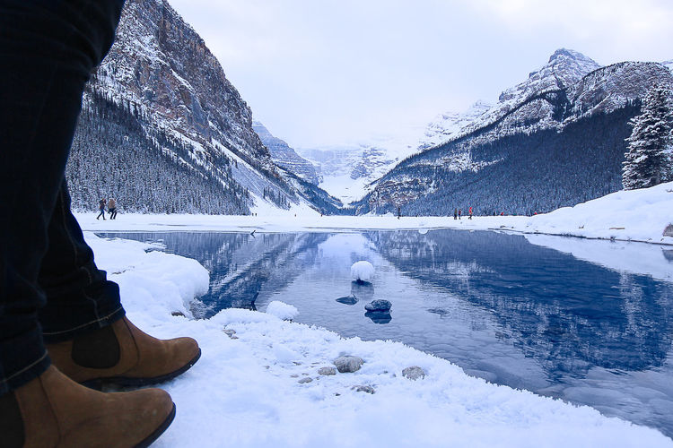 Low Section Of Person Standing By Lake During Winter Against Mountains