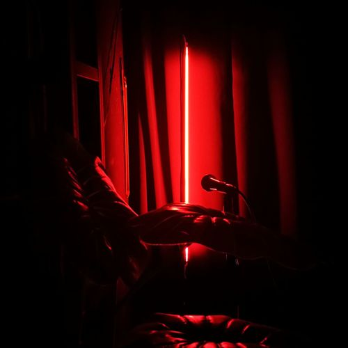 Midsection of man with red light in dark room