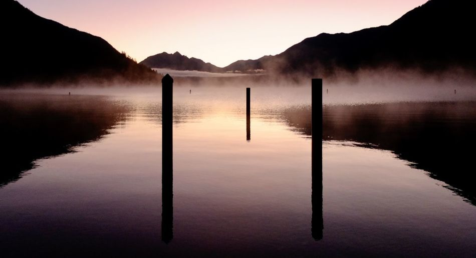 Wooden posts in lake against sky during sunset
