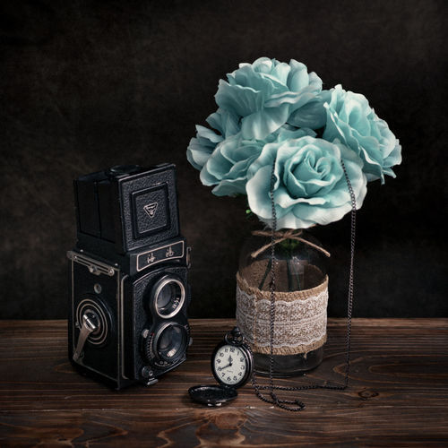 Close-up of camera and pocket watch with turquoise flowers on table