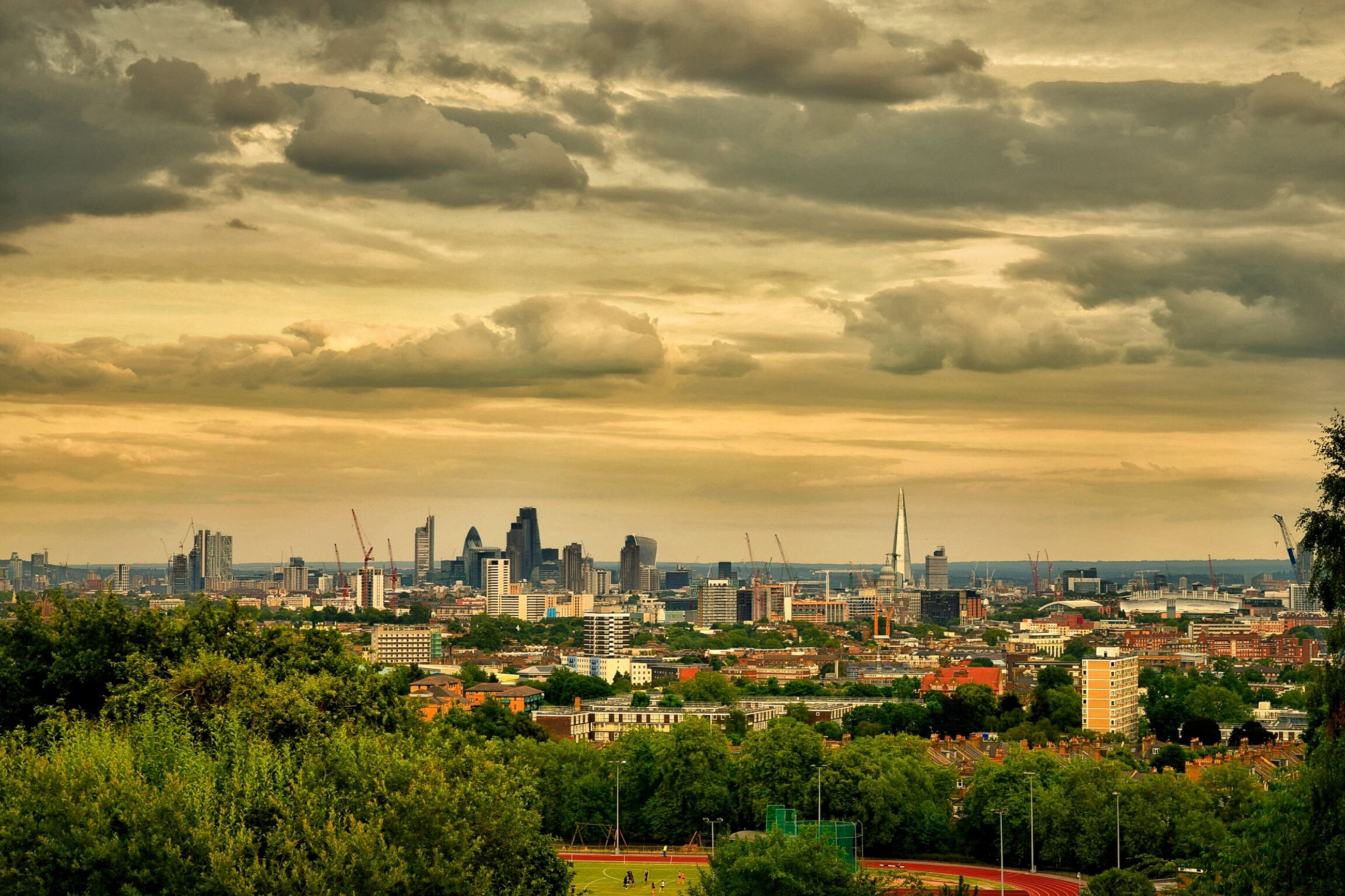 building exterior, architecture, cityscape, built structure, sky, city, cloud - sky, tree, high angle view, residential district, crowded, residential building, cloudy, residential structure, cloud, growth, sunset, landscape, nature, outdoors
