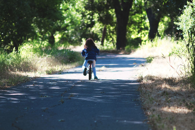 Rear View Full Length Of Girl Riding Bicycle On Road