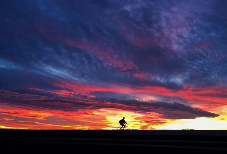 Silhouette man against orange sky