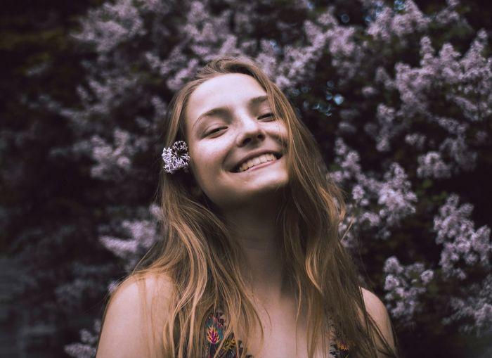 Portrait of smiling teenage girl against flowering plants at park