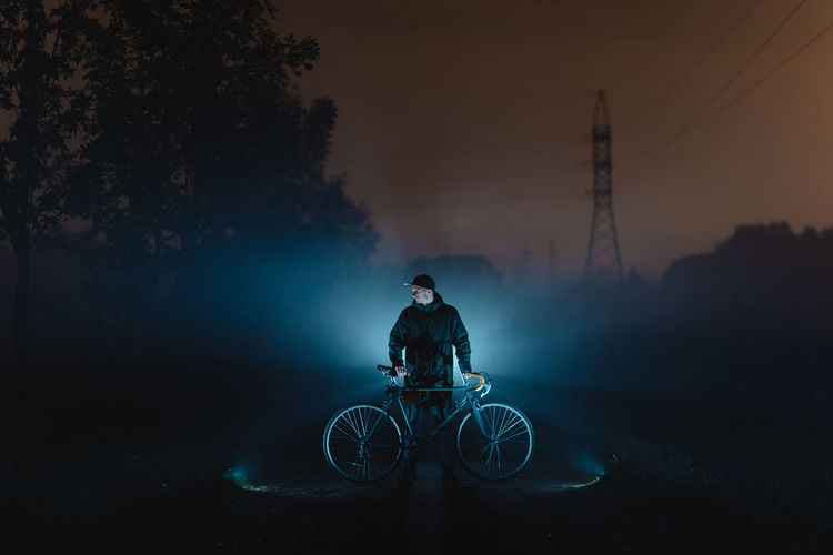 Man With Bicycle Against Illuminated Light Standing On Road At Night