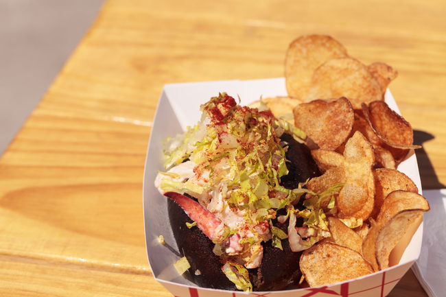 Gourmet Maine Lobster roll on a pumpernickel bun and potato chips at the beach in summer. Bread Cole Slaw Fish And Chips Gourmet Lobster Lobster Roll Lunch Potato Chips Pumpernickel Roll Seafood Shellfish🐚 SLAW