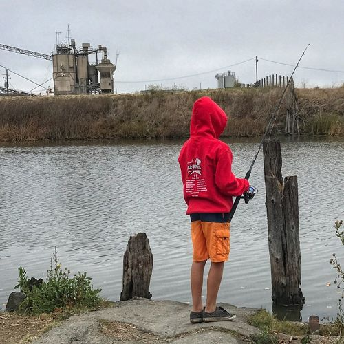 Water Day Rear View Full Length One Person Real People Lake Outdoors Built Structure Sky Leisure Activity Standing Nature Lifestyles Building Exterior Architecture Warm Clothing People Fishing Fishing Time Boy Fishing Red Jacket
