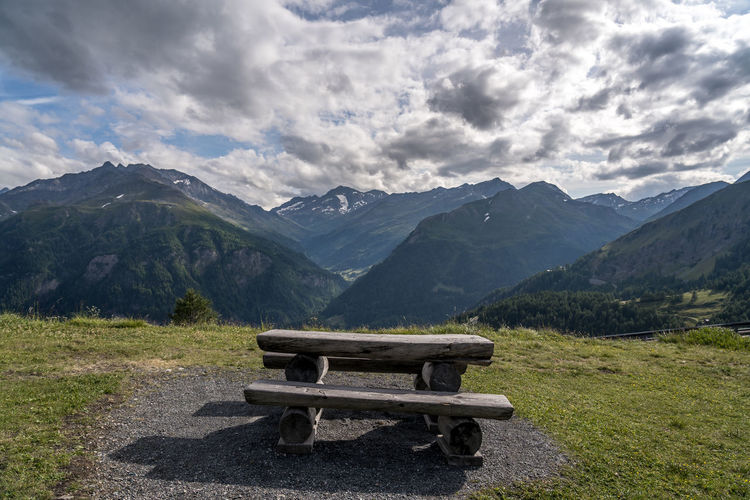 Empty bench on mountain range against sky