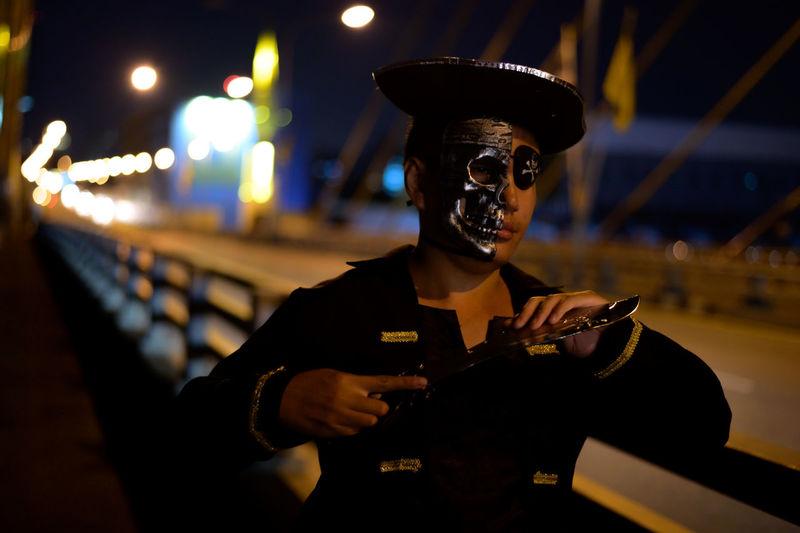 Young man wearing pirate costume standing on bridge at night
