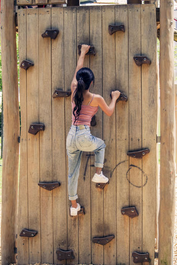 Full length rear view of woman climbing on artificial wall