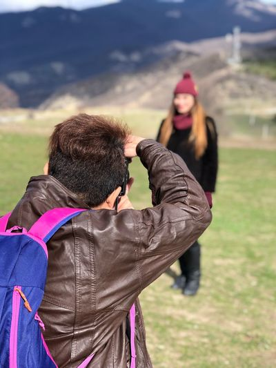Rear view of man photographing female friend standing on landscape