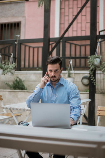 Young businessman talking on mobile phone while using laptop on table