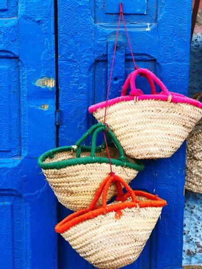 Close-up of clothes hanging on rope against blue wall
