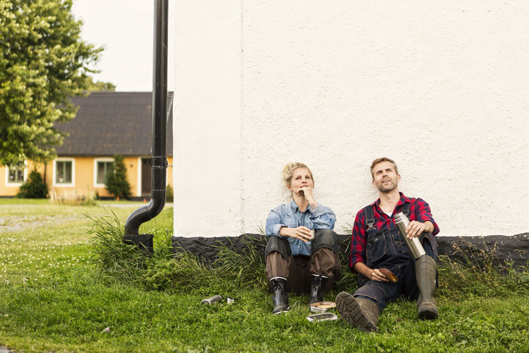 Full length of men sitting on grass against wall