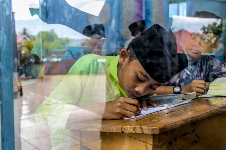 Boys Studying At Table Seen Through Window