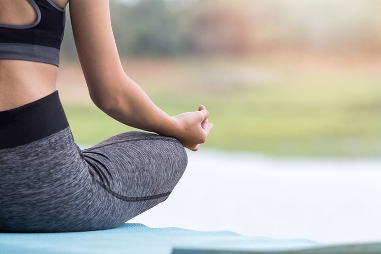 Low Section Of Woman Practicing Yoga On Grass At Park