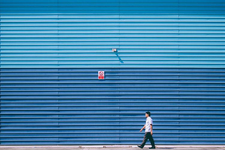 Man Walking By Blue Shutter In Sunny Day