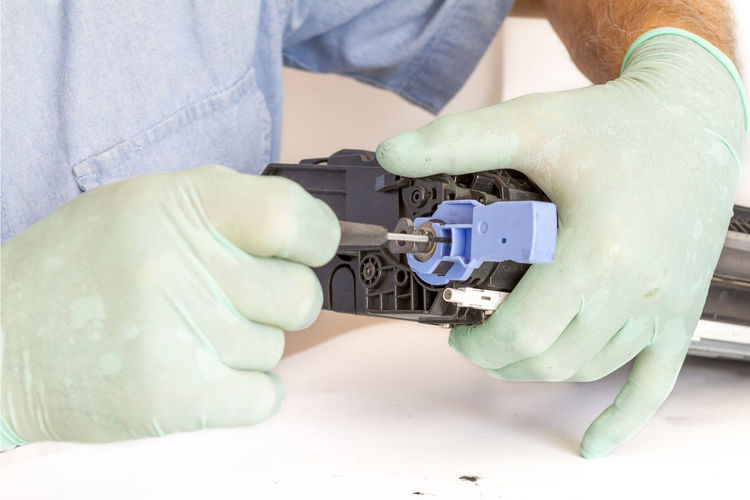 Midsection Of Man Repairing Machine Part