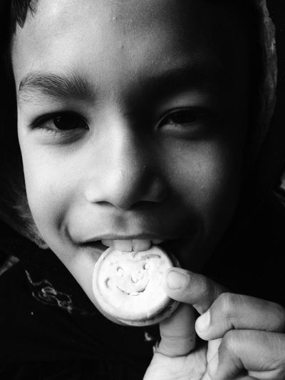 Close-Up Of Boy Eating Biscuit