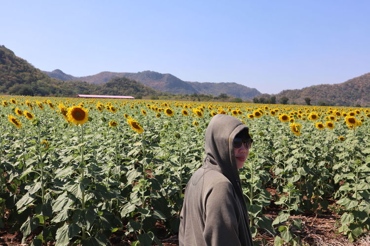 Portrait of woman standing against sunflower field during sunny day