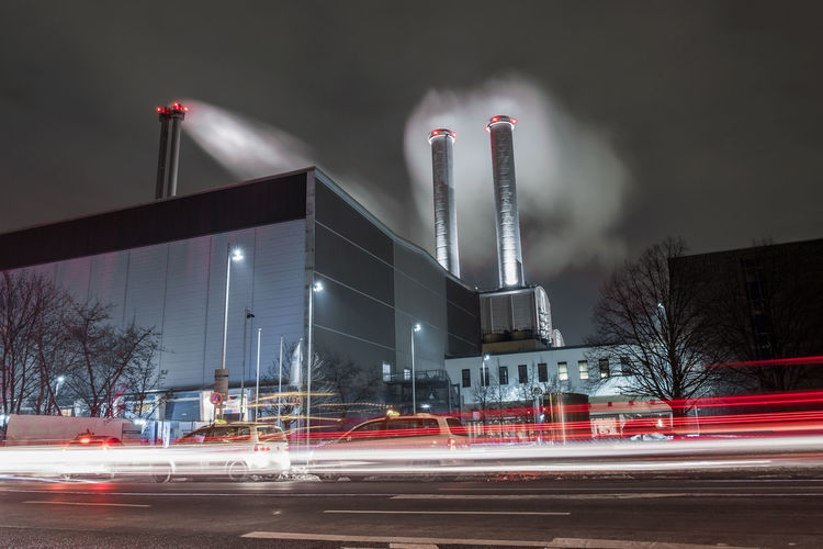 Light trail on street by smoke stacks emitting pollution