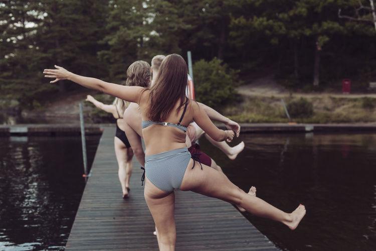 Rear view of woman in bikini standing by lake